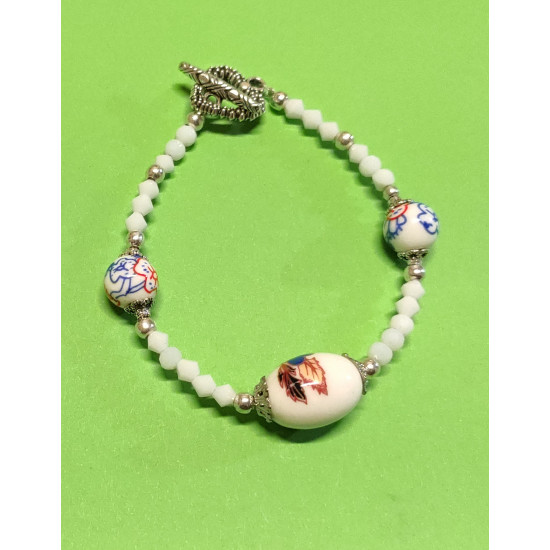 Bracelet about 19-20 mm. Matt white glass biconical crystals, oval porcelain beads with blue flowers, spherical porcelain beads with popcorn, silver balls and Tibetan silver caps. The bracelet is handmade on silicone wire with toggle clasps