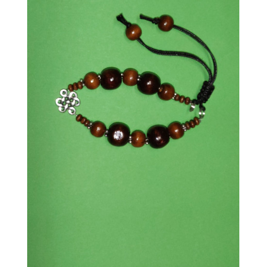 Bracelet. Dark brown wood spheres beads, Tibetan spacer with beads and Tibetan link, mystical knot. The bracelet is handmade on silicone wire and black waxed cord.