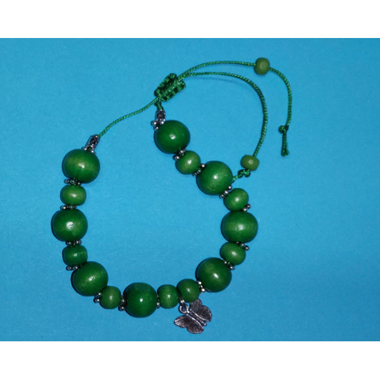 Bracelet. Wooden oval beads, green, Tibetan spacer with beads and butterfly charm. The bracelet is handmade on a green waxed cord.