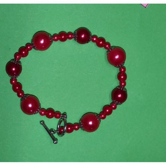 Red glass beads and Tibetan silver caps. The bracelet is handmade on silicone wire with Tibetan toggle clasps. Length approx. 21.5 cm.