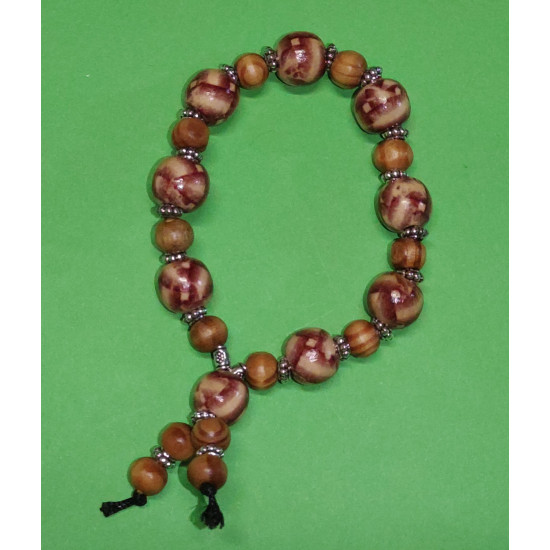 Bracelet. Wooden beads with brown dashes, Tibetan silver spacer and. The bracelet is made by hand on an elastic cord.
